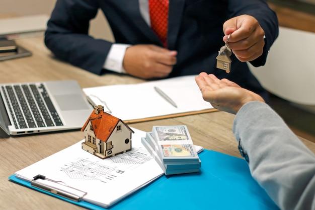 Agente de bienes raíces con casa modelo y llaves