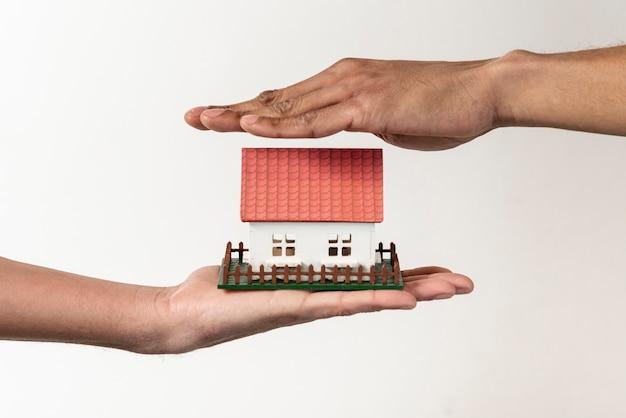 Agente de bienes raíces y cliente sosteniendo una casa de juguetes