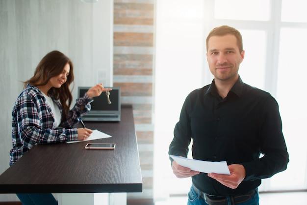 Agente de bienes raíces, corredor o arrendador le muestra un departamento a una joven. ella va a firmar un contrato de arrendamiento con él.