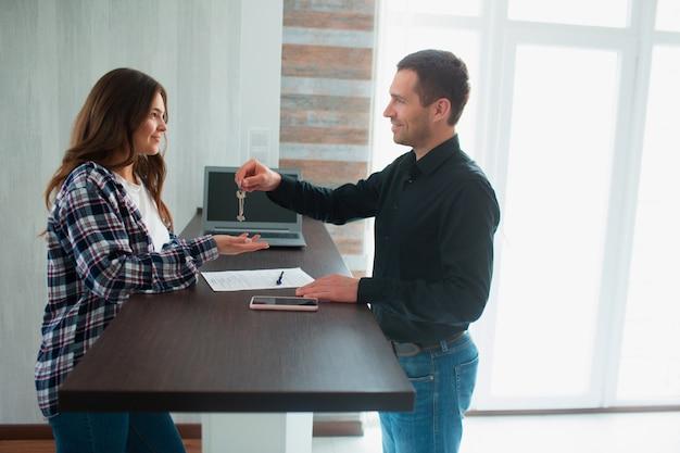 Agente de bienes raíces, corredor o arrendador muestra un departamento a una joven