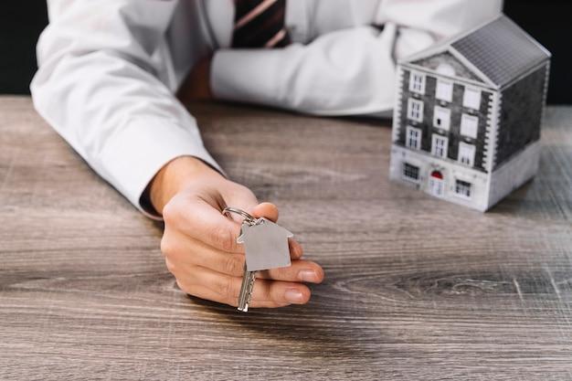 Agente de bienes raíces de cultivos mostrando nueva clave