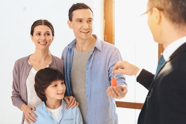 El agente de bienes raíces está dando las llaves de un nuevo apartamento para la familia.