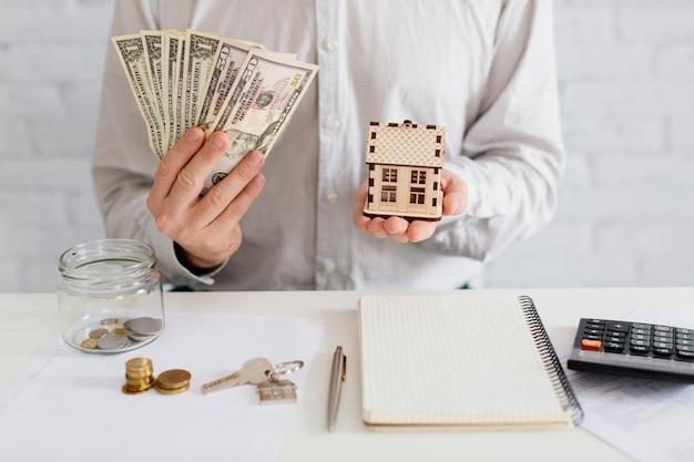 Agente de bienes raíces con dinero y casa de madera