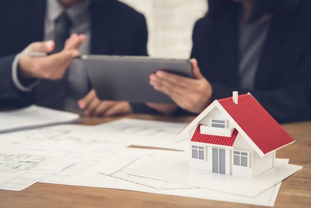 Agente de bienes raíces discutiendo el trabajo con planos y modelo de casa sobre la mesa