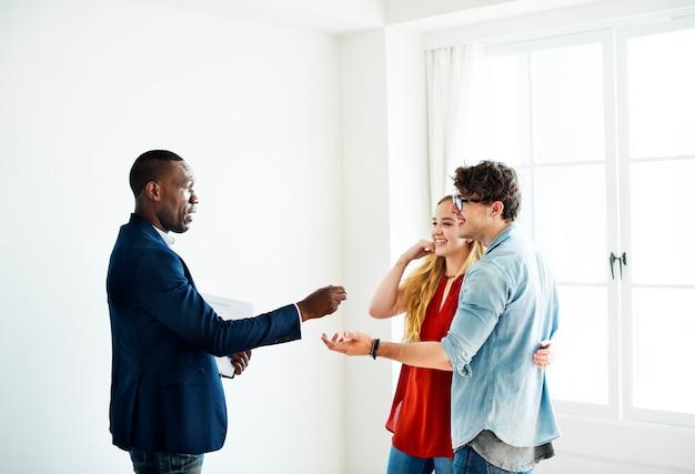 Agente de bienes raíces entregando la llave de la casa a los clientes.