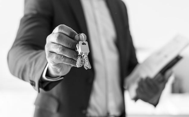 Agente de bienes raíces entregando la llave de la casa