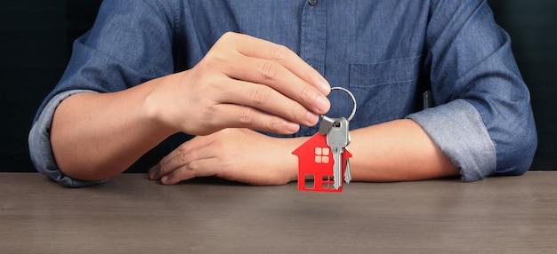 Agente de bienes raíces entregando las llaves de una casa en la mano