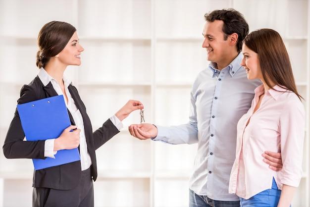 Agente de bienes raíces femenino está dando a la pareja una clave del nuevo piso.