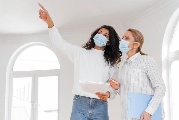 Agente de bienes raíces femenino con máscara médica que muestra la casa a la mujer