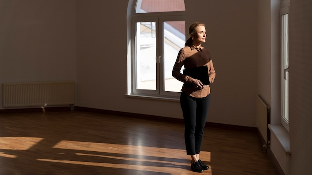 Agente de bienes raíces femenino de pie en la casa vacía y mirando por la ventana con espacio de copia