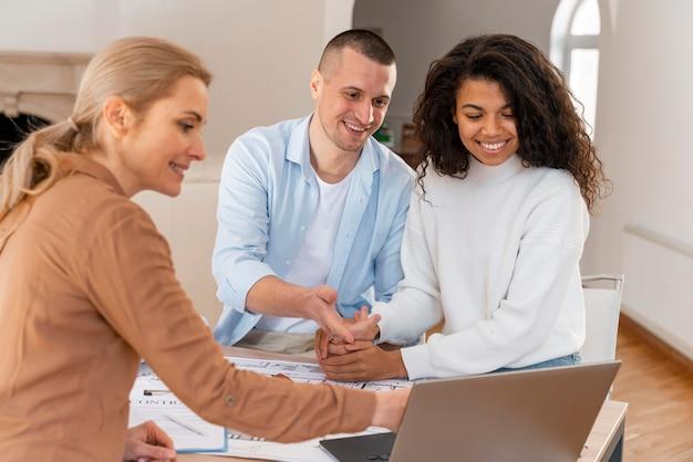 Agente de bienes raíces femenino que muestra la nueva casa a la pareja sonriente en la computadora portátil