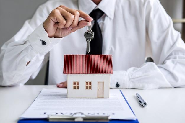 Agente de bienes raíces gerente de ventas sosteniendo las claves de presentación al cliente después de firmar el alquiler