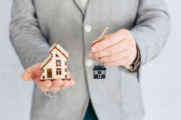 Agente de bienes raíces con llave y casa pequeña