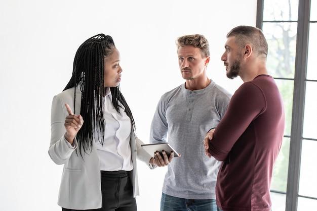 Agente de bienes raíces de mujer hablando con clientes de pareja gay
