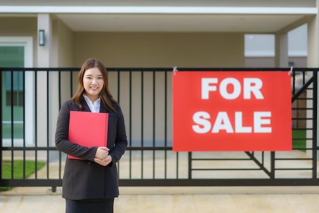 Agente de bienes raíces de mujeres asiáticas está de pie frente a la casa con un cartel de venta colgado en la puerta