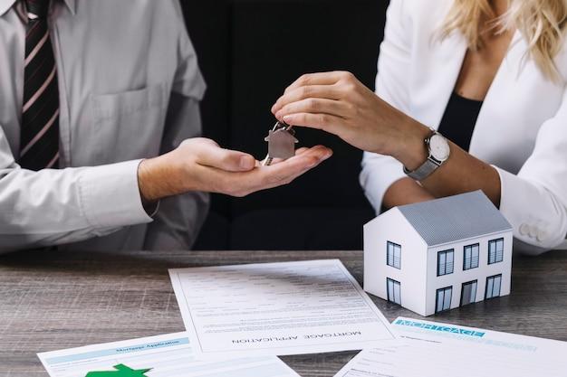 Agente de bienes raíces pasando la llave al nuevo propietario