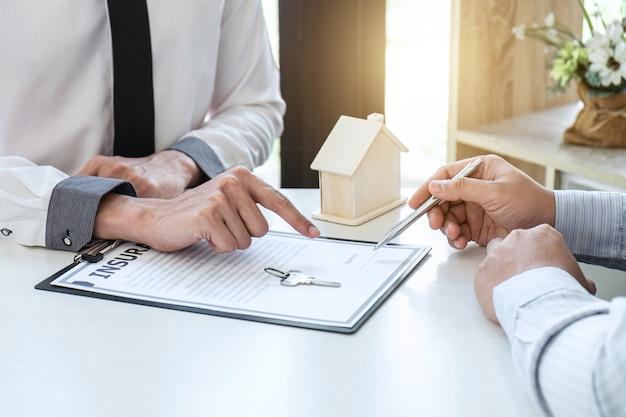 El agente de bienes raíces presenta un préstamo hipotecario y le da las llaves al cliente después de firmar el contrato para comprar