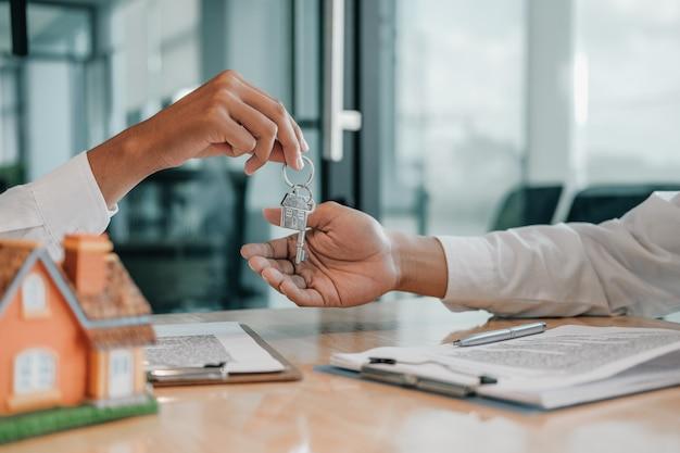 Agente de bienes raíces que da la clave de inicio al cliente. compra venta alquiler propiedad inmobiliaria