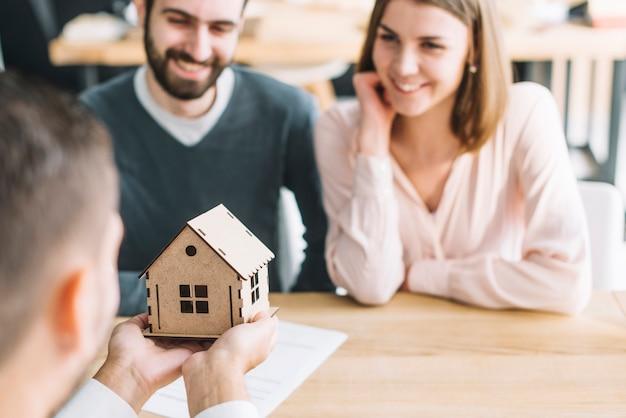 Agente de bienes raíces que muestra casa de juguete para pareja