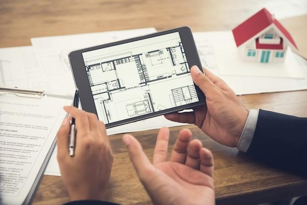 Agente de bienes raíces que presenta el plano de planta al cliente en una tableta