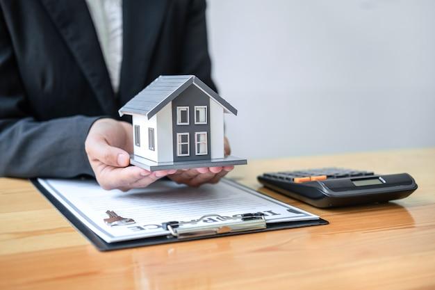 Agente de bienes raíces que trabaja firma acuerdo documento contrato para seguro de casa aprobando compras
