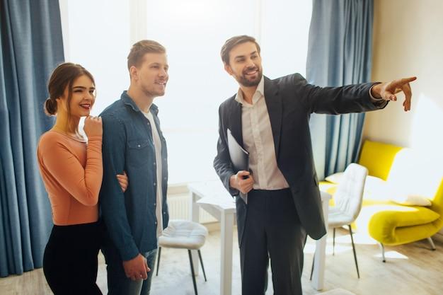 Agente de bienes raíces señalando algo y hablando con la pareja