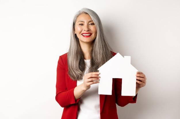 Agente de bienes raíces de sexo femenino asiático que muestra el recorte de la casa de papel, corredor que sonríe amable y que vende la propiedad, de pie sobre el fondo blanco