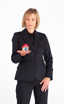 Agente de bienes raíces sosteniendo una casa