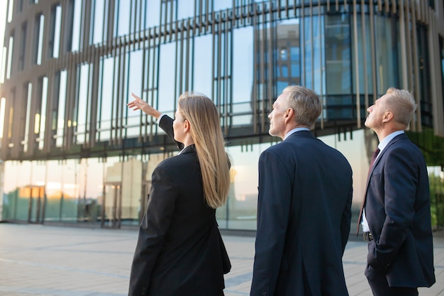 Agente y clientes reunidos al aire libre, discutiendo bienes inmuebles, apuntando al edificio de oficinas. vista trasera. concepto de bienes raíces comerciales