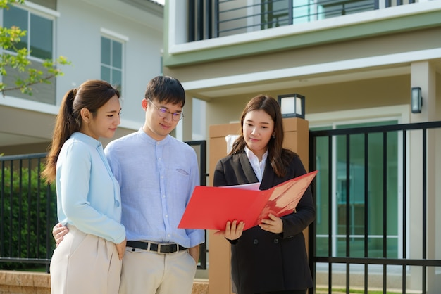 Agente de corredor de bienes raíces mujer asiática mostrando un detalle de la casa