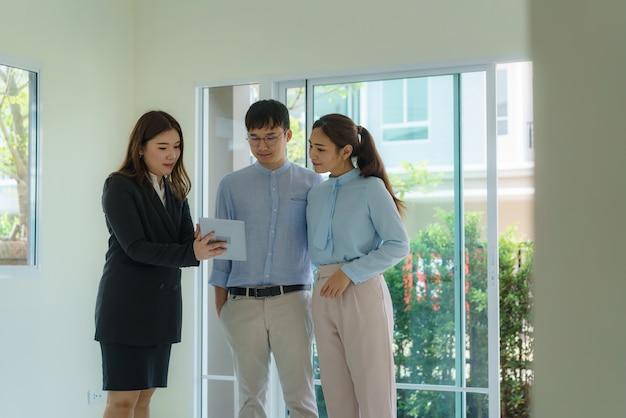 Agente de corredor de bienes raíces de mujer asiática que muestra un detalle de la casa en su tableta digital