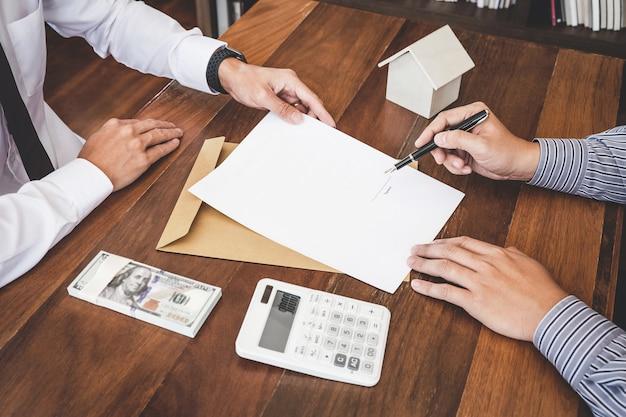Agente de corredores que presenta y consulta los detalles al cliente para tomar la decisión sobre un préstamo inmobiliario para firmar un acuerdo de formulario