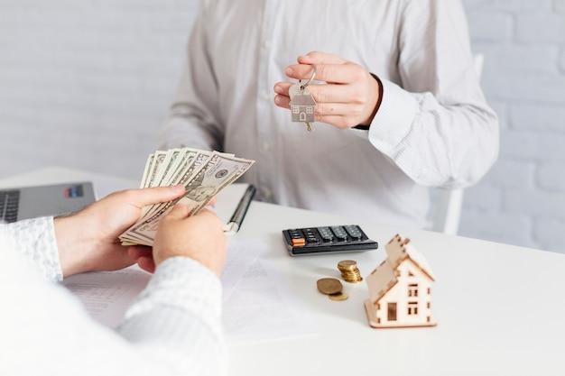 Agente de bienes raíces dando llaves y tomando dinero