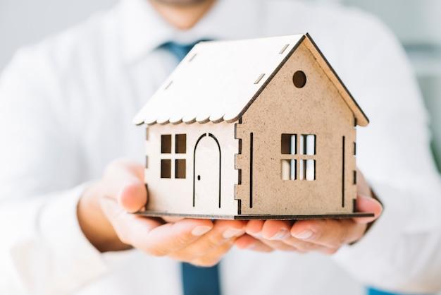 Agente de bienes raíces de close-up con casa de juguete