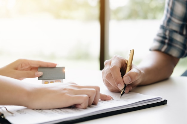 El agente estatal otorga un acuerdo de pluma y documentos con el cliente para firmar el contrato.