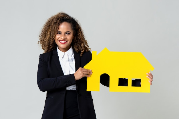 Agente feliz sosteniendo la casa amarilla