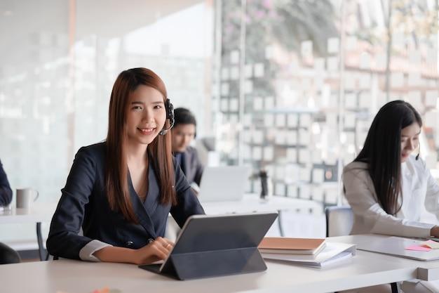 Agente femenino asiático hermoso del centro de atención telefónica en cliente de la consultoría de las auriculares.