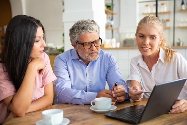 Agente femenino positivo que muestra la presentación del proyecto en una computadora portátil a una mujer joven y un hombre maduro, apuntando el lápiz a la pantalla, explicando los detalles
