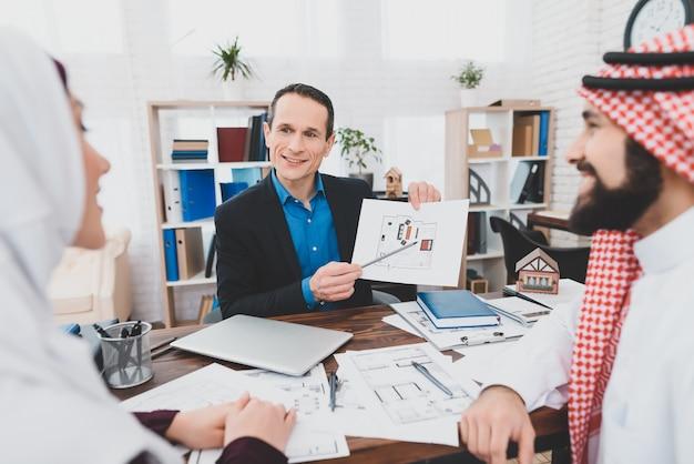Agente hipotecario muestra el plano de la casa a los clientes.