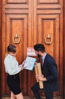 Agente inmobiliario y arquitecto con puerta de madera