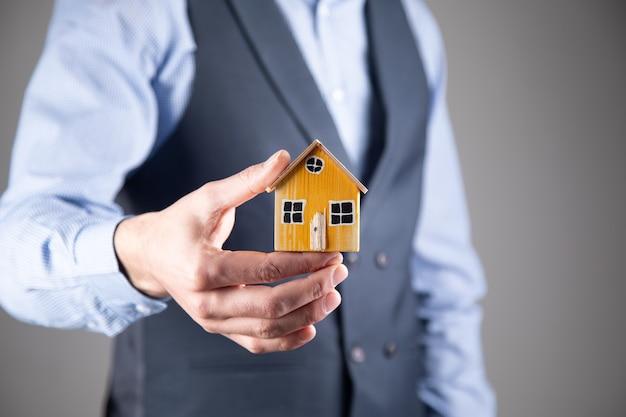 Agente inmobiliario, casa de madera en manos masculinas.