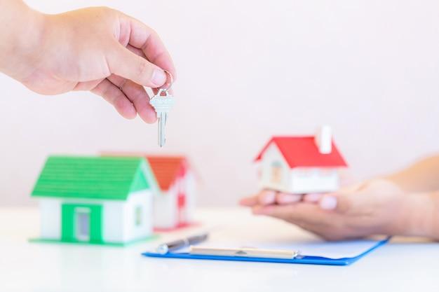 Agente inmobiliario con casa modelo y llaves.