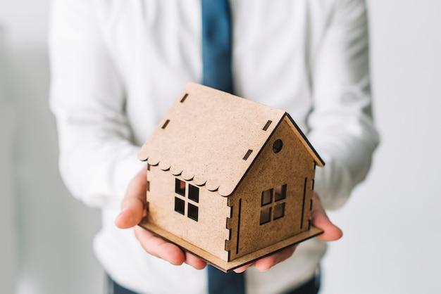 Agente inmobiliario de cultivo que sostiene la casa