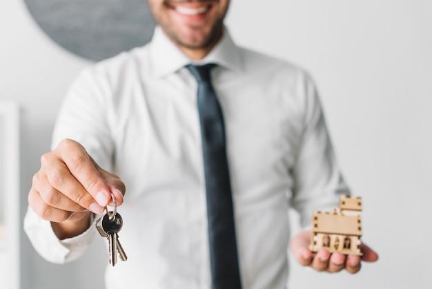 Agente inmobiliario de cultivos con llaves y casa