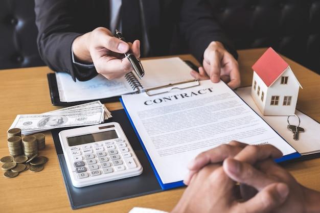 El agente inmobiliario le da un bolígrafo al cliente que firma el contrato de patrimonio con el formulario de aprobación