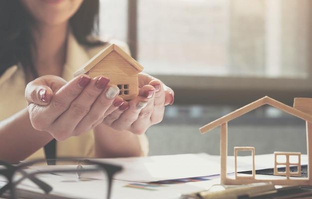 El agente inmobiliario le da a la casa modelo un acuerdo con el cliente para firmar el contrato. concepto de seguro