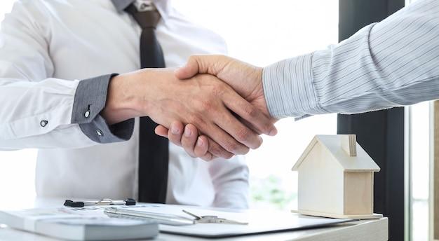 El agente inmobiliario se da la mano después de un buen trato y le da a la casa las llaves del cliente