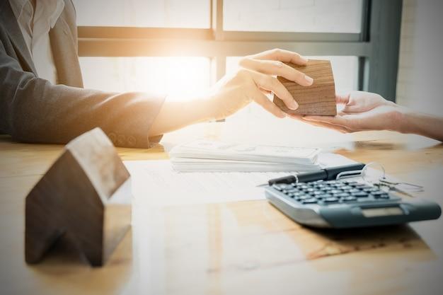 Agente inmobiliario dando la casa al cliente después de la firma del contrato. concepto de acuerdo.