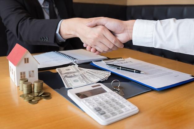 Agente inmobiliario desarrollador y firmar en el documento dando las llaves de la nueva casa
