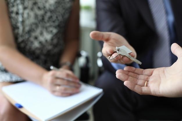 El agente inmobiliario está entregando la llave del apartamento nuevo
